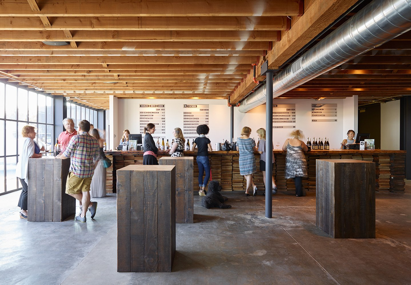Lounge with exposed wood joists, sliding black steel wall panels, salvaged wood cocktail tables and stacked wood bar.