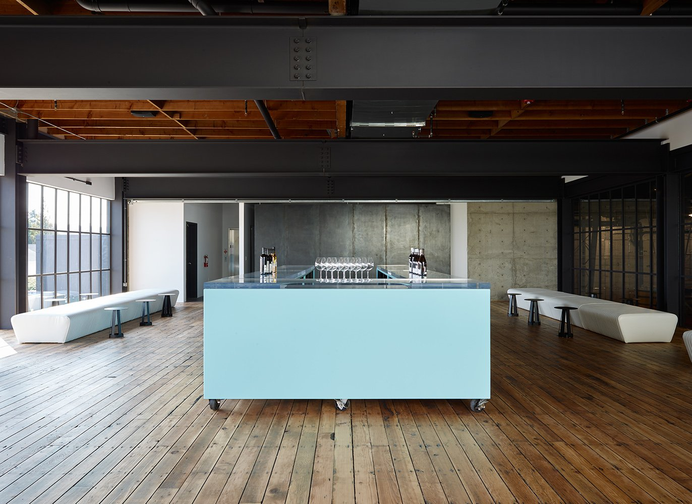 White tuck-an-roll upholstered perimeter seating and powder-blue Lucite-topped bar on wheels in the upstairs tasting room.