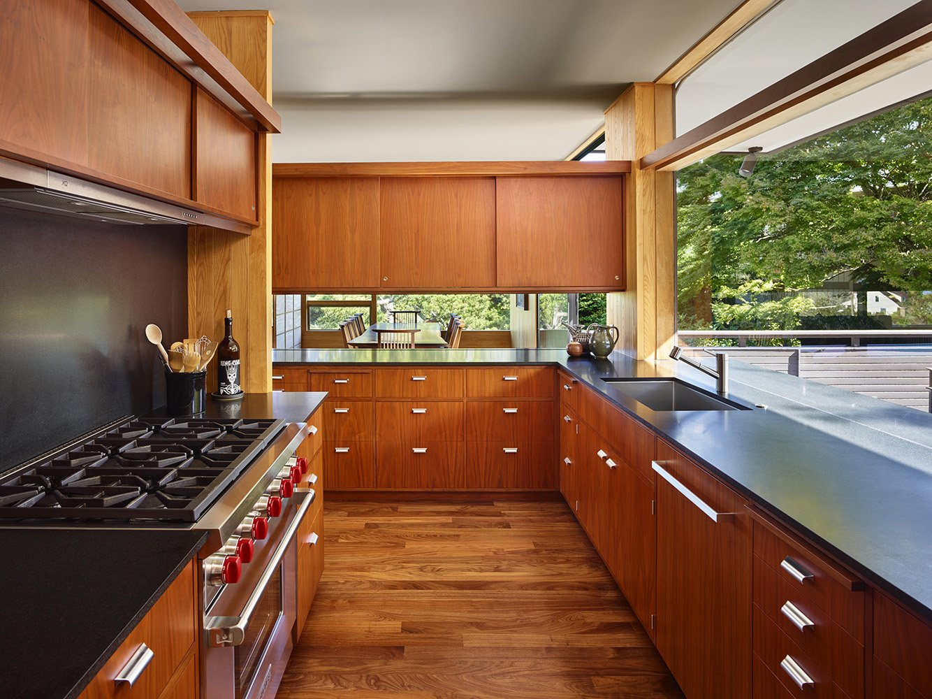 A Wolf range, its exhaust venting hidden by new casework, is surrounded by walnut cabinets and cupboards designed to match the originals