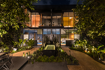 Wide view of the backyard and facade of the completely new building at night Jaime Navarro