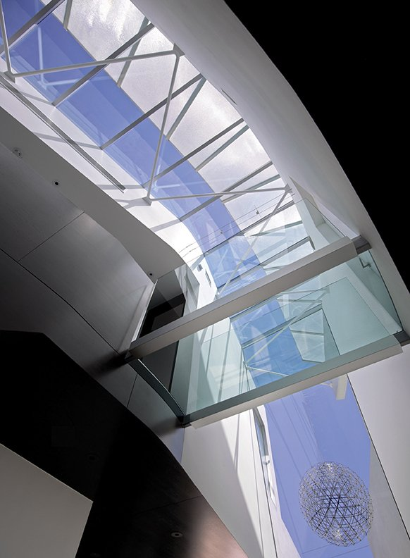 Looking curved skylight and glass floor from below }
