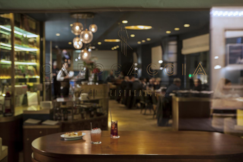 Vista dall'esterno del locale, zona bar. in primo piano tavolo in legno realizzato su disegno da artigiani italiani