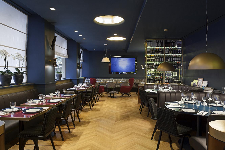 Vista della zona bistrot con tavolini, banquette e poltroncine imbottite