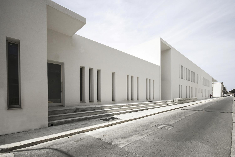 Sulla strada laterale il complesso parrocchiale si presenta con un carattere introverso con delle fessure che filtrano il rapporto con la strada  arch. Benedetta Fontana