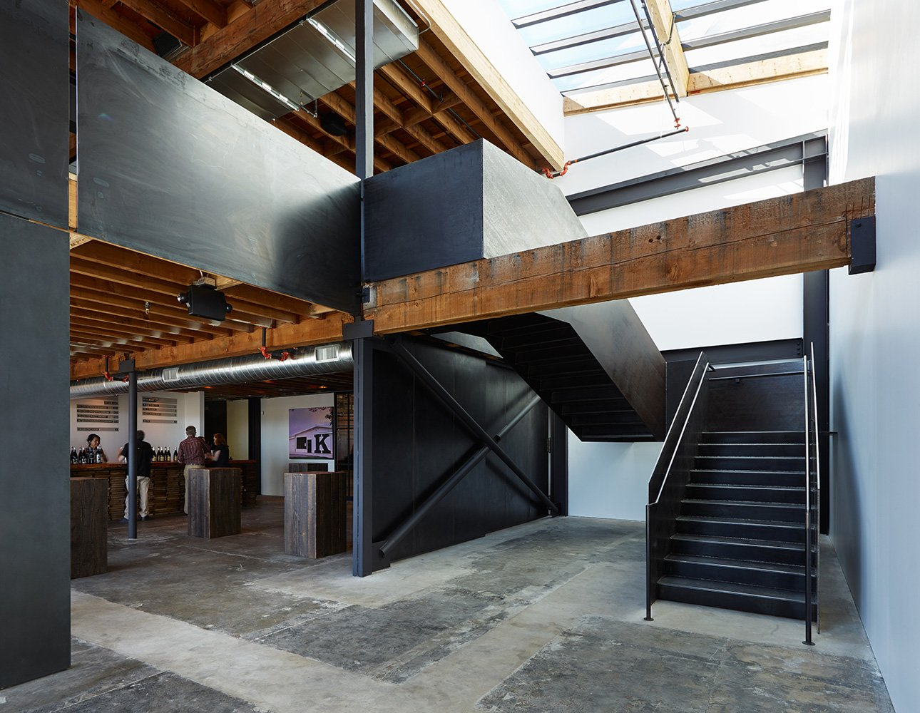 A plate-steel staircase connects the first-floor lounge to the expansive second-floor tasting room.