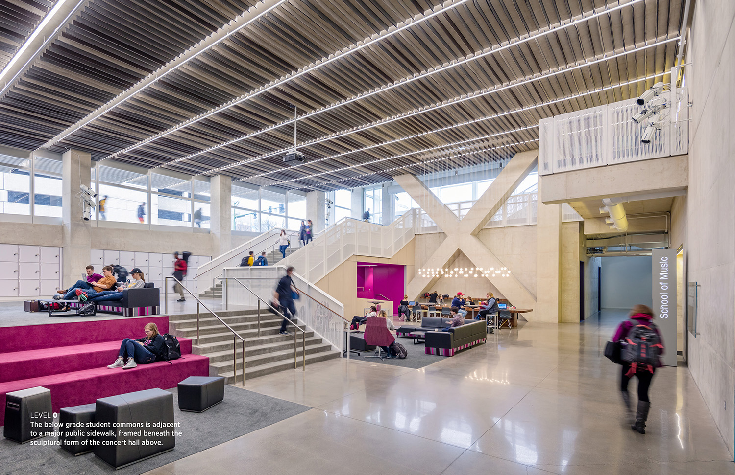 The below grade student commons is adjacent to a major public sidewalk, framed beneath the sculptural form of the concert hall above. Tim Griffith}