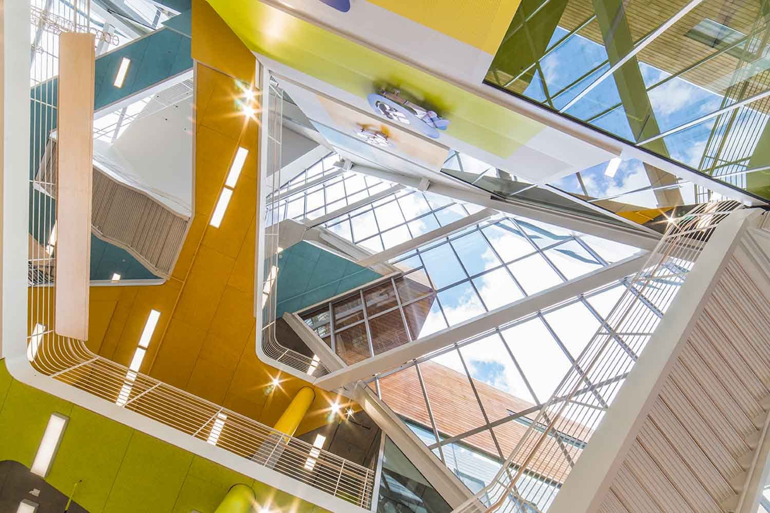 Atrium space looking up. The colors and building form help fuse urban activity with campus life. Janis Rozkalns