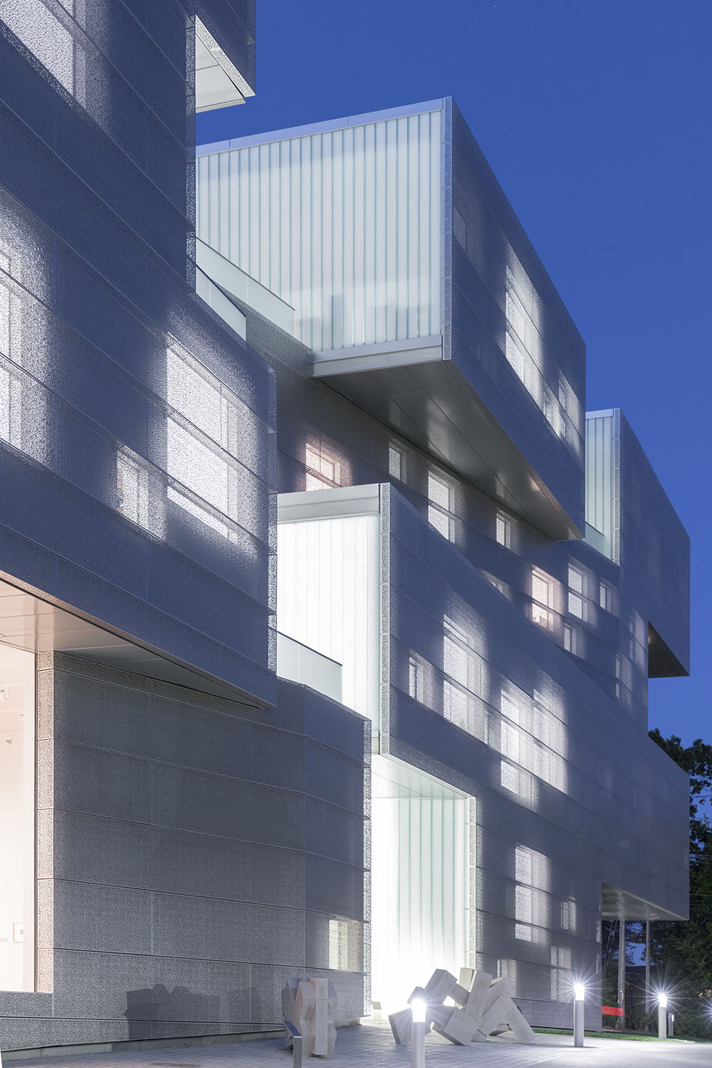 Exterior night view showing punched stainless steel perforated panels emitting soft diffused light.
