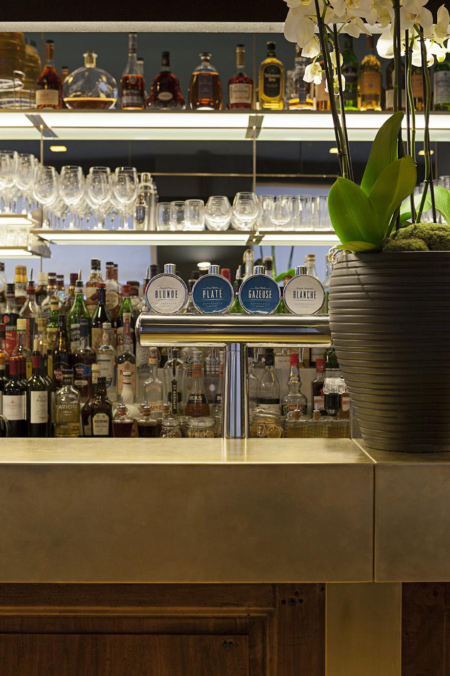 Vista di dettaglio del bar in ottone e legno, retro bar realizzato con specchi e mensole in vetro retroilluminate