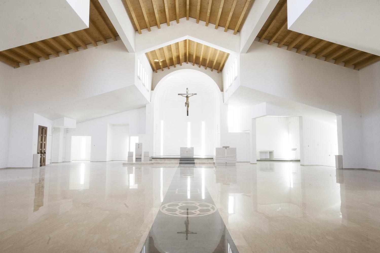Un tappeto intarsiato in marmo conduce al presbiterio, volumi bianchi, luce, copertura in legno arch. Benedetta Fontana