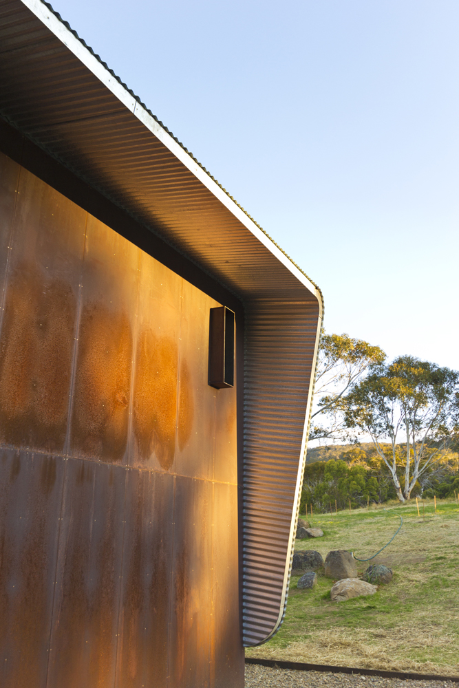 Weathered steel end facade + corrugated roof / wall wrapping detail