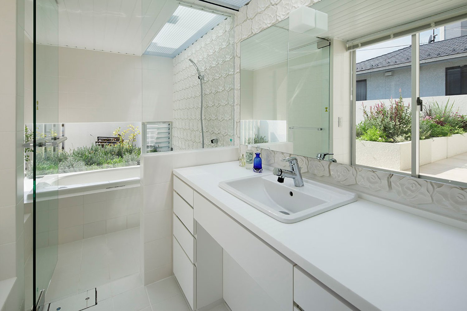 Bath room. A white and clean space. Light pours from the top light. }