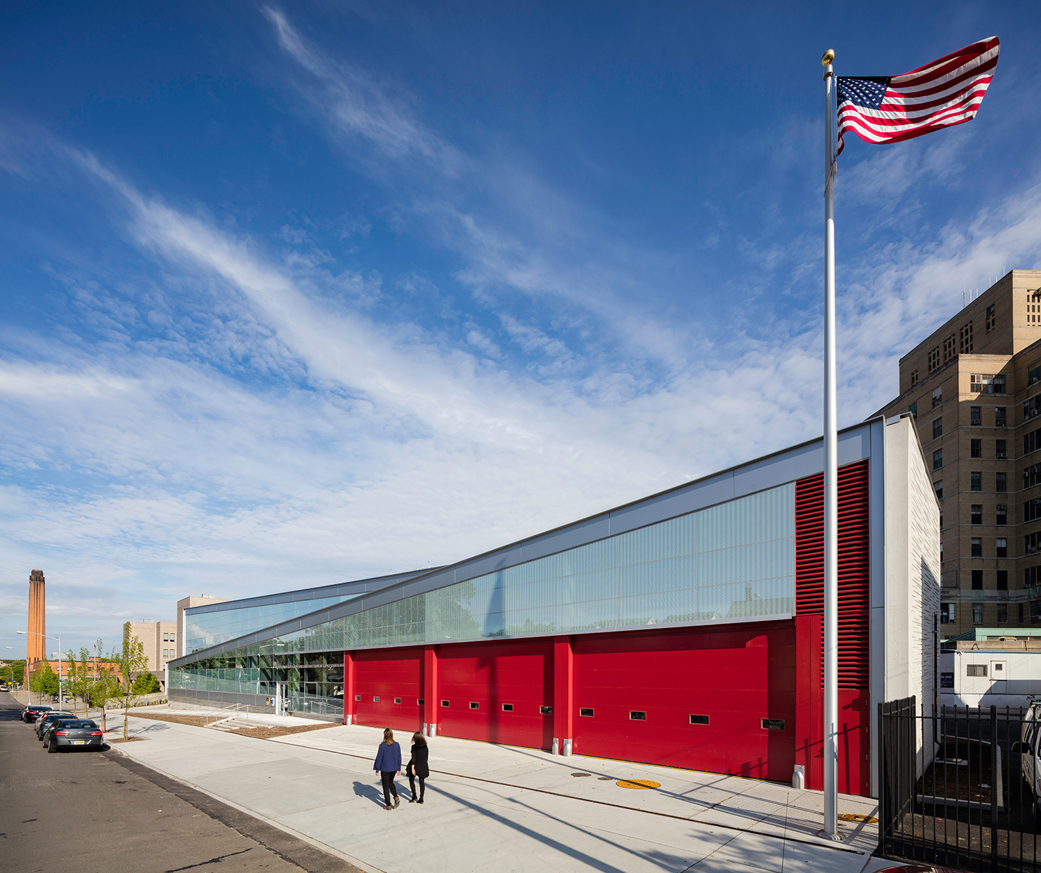 The apparatus floor, located at the hinge in the folded form, is the joint between interior and exterior. The signature FDNY-red overhead garage doors are the focal point of the street façade. Paul Warchol