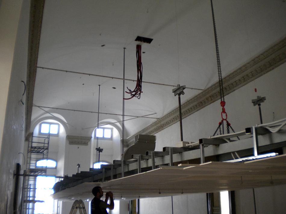 fase di montaggio del controsoffitto alla struttura portante. Il Plafone durante l'allestimento veniva calato con delle catene direttamente dai fori degli ex lampadari inseriti nella volta. }