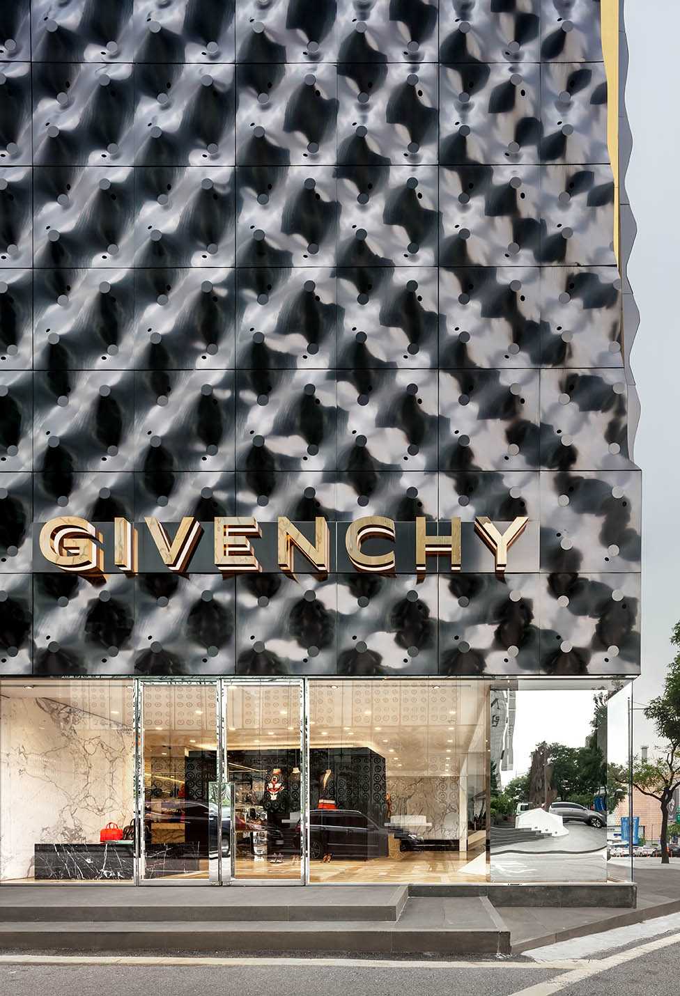 Vista dalla strada, la trasparenza del volume vetrato crea un forte contrasto con il volume superiore materico caratterizzato dai pannelli ondulati che riflettono il dinamismo cittadino.