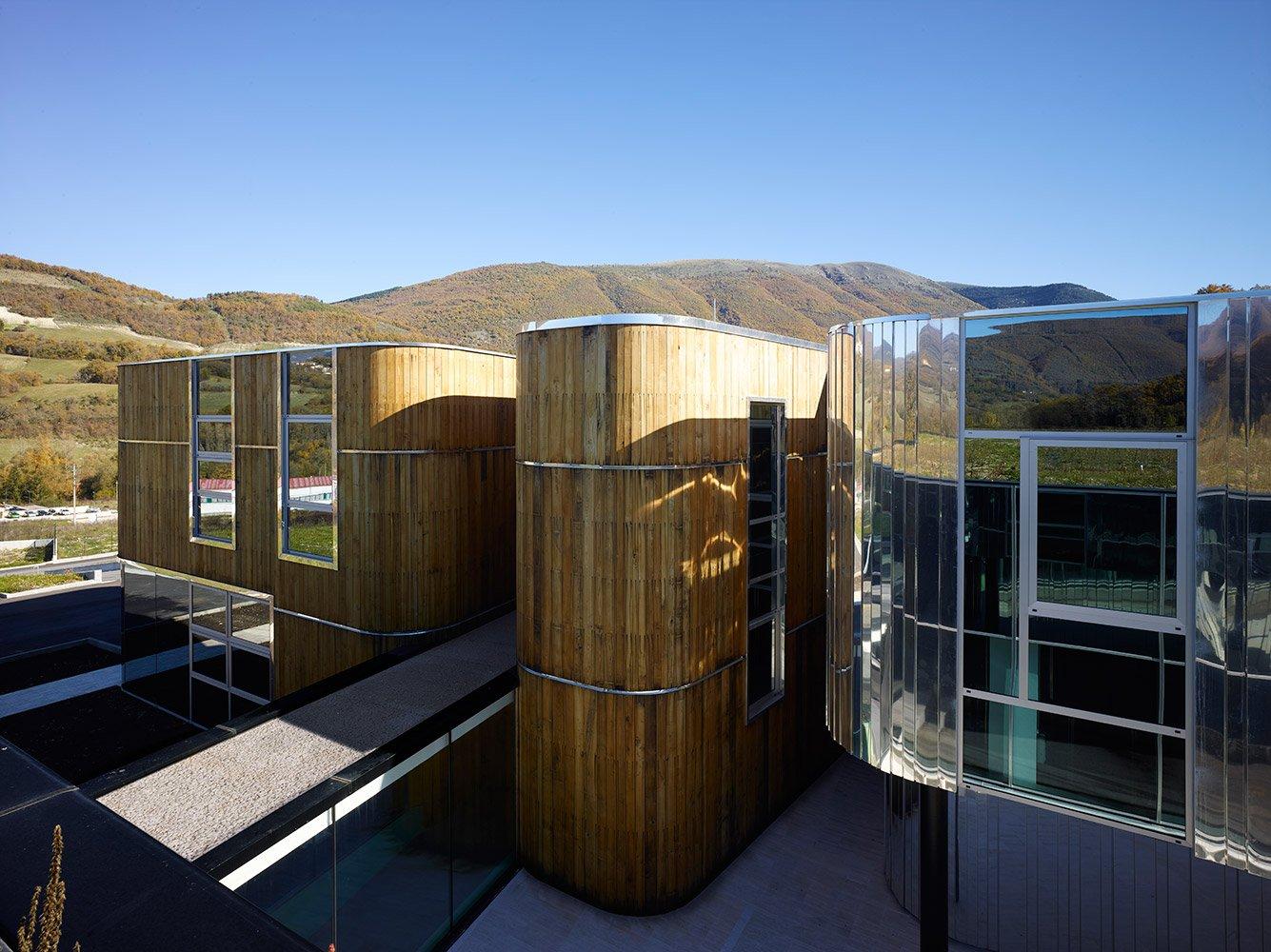 vista del direzionale, volumi rivestiti in legno, acciaio inox e vetro, connesso alla parte produttiva mediante un tunnel di collegamento vetrato