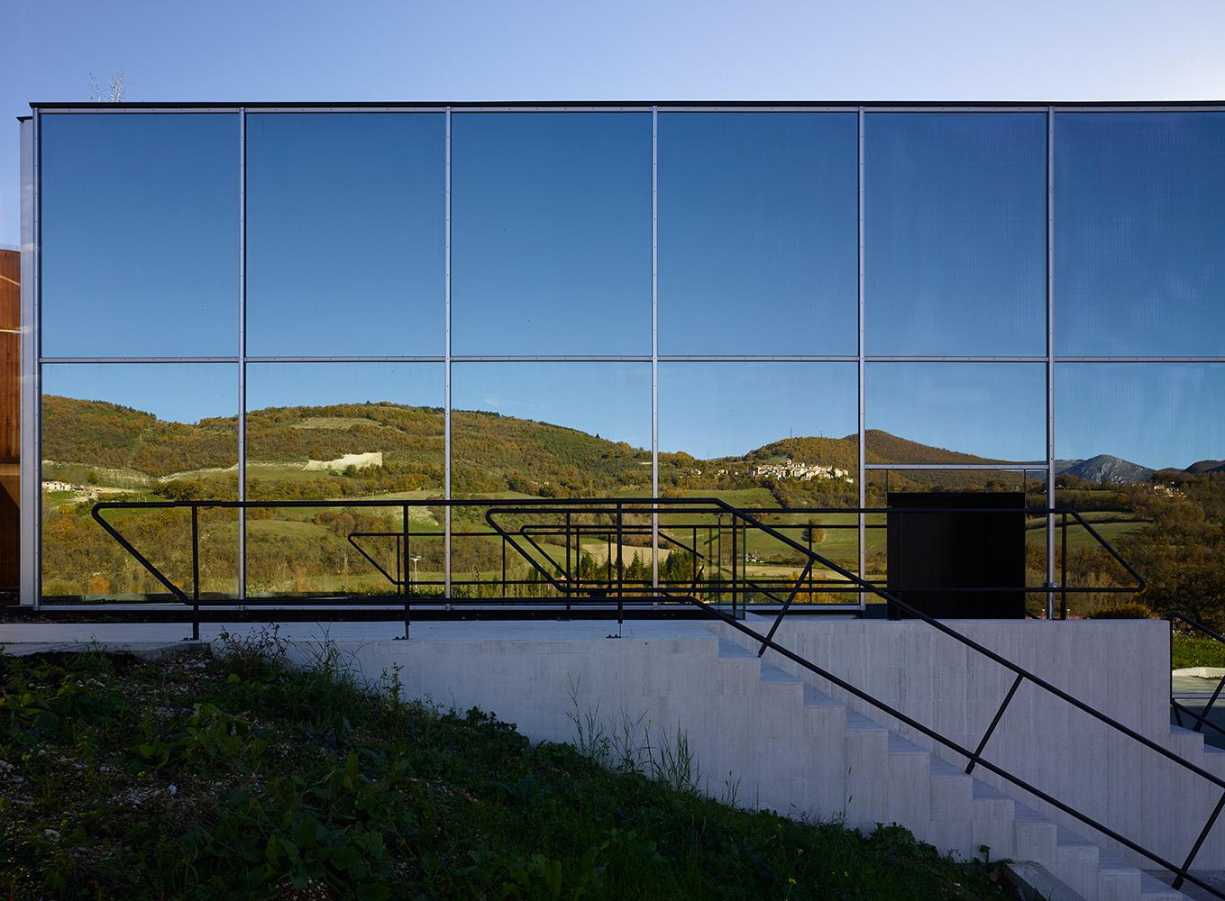 """dettaglio del fronte nord dello stabilimento produttivo, rivestito con vetro specchiante per riflettere la vegetazione ed il paesaggio circostante, al fine di mimetizzare """"l'artificio"""" dell'opificio con la"""