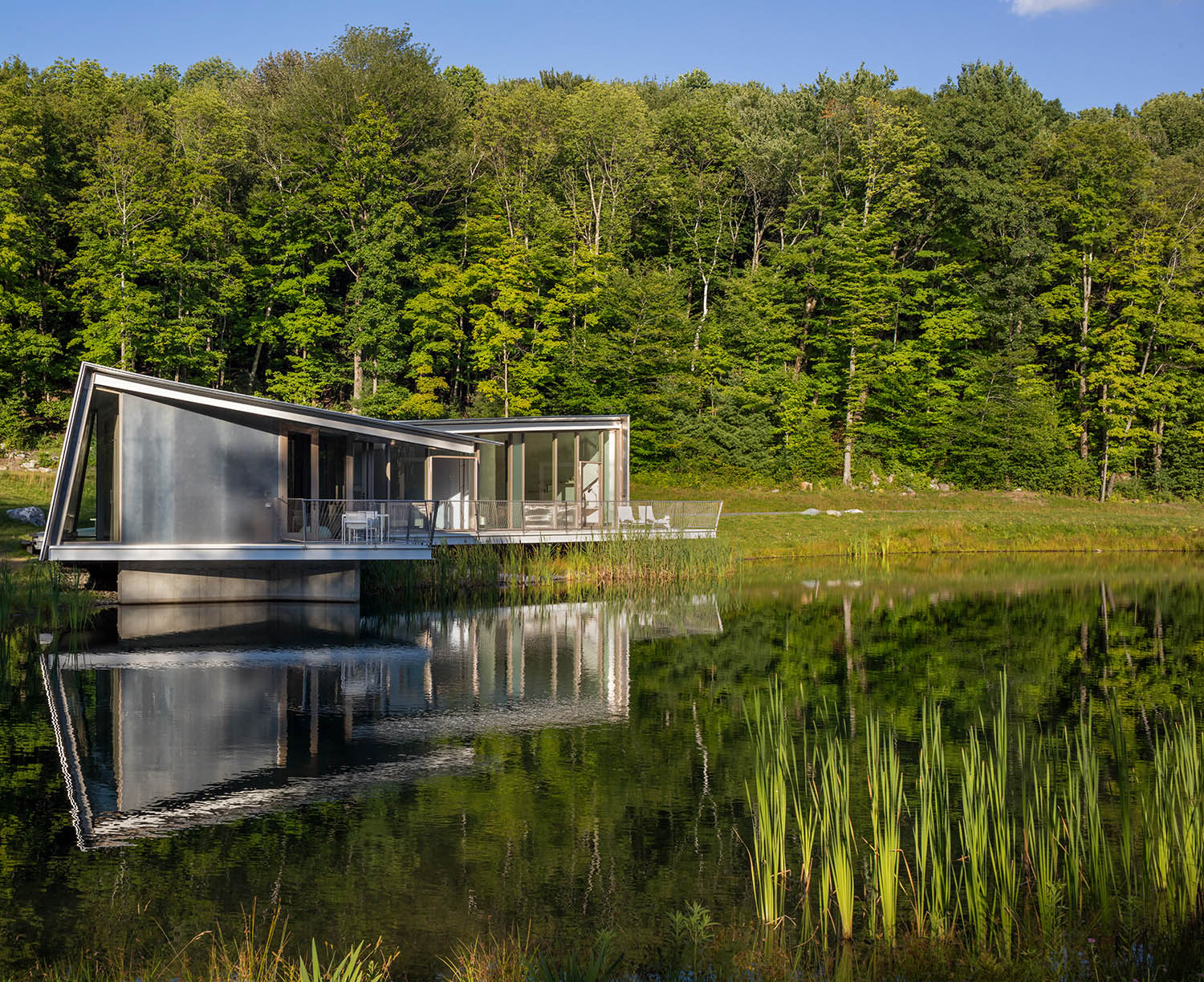 The lightness and delicacy of the forest and reeds is reflected in the floating posture of the house, suspended above the water on five pier foundations.  Paul Warchol