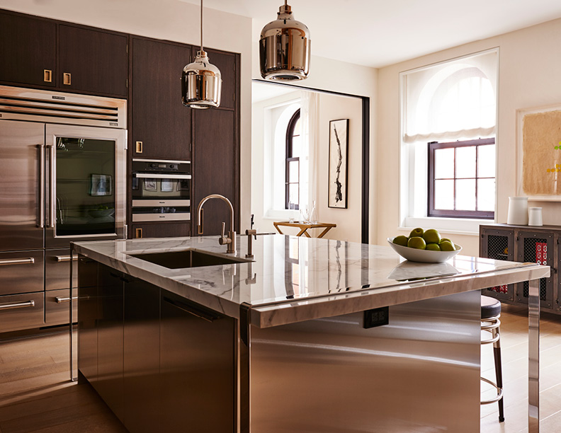 Large stainless steel island topped with a marble counter top that is accented by polished metal legs and strap details  Adrian Gaut
