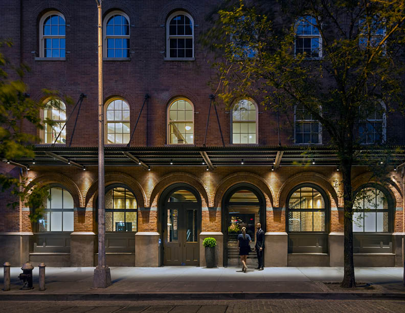 Restored building entrance canopy in relationship to streetscape, preserving the Romanesque elements found in German round-arch style windows and doors  David Sundberg