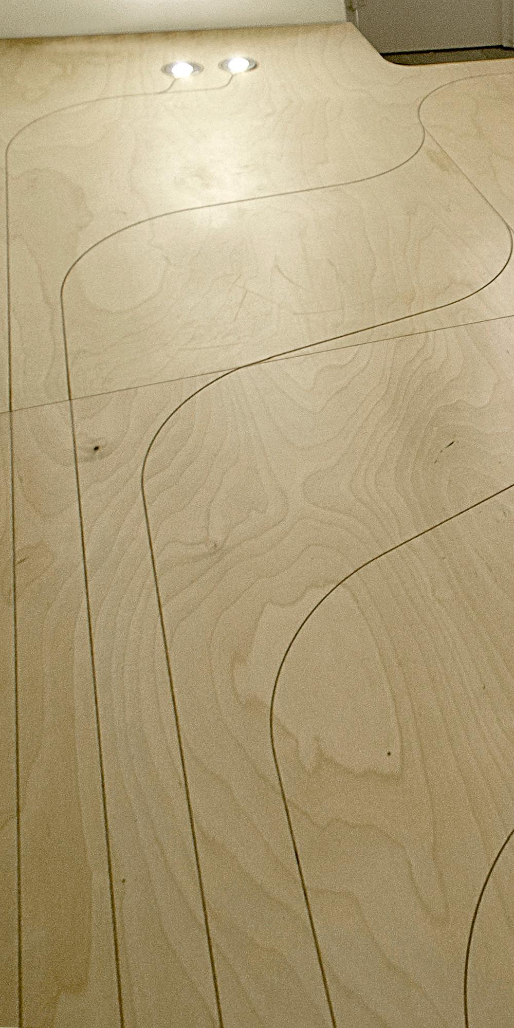 Dettaglio della finitura del pavimento in multistrato di Betulla. La superficie libera è stata incisa come se si trattasse di un tappeto. La trama continua si sviluppa addensandosi e diradandosi sul piano  }