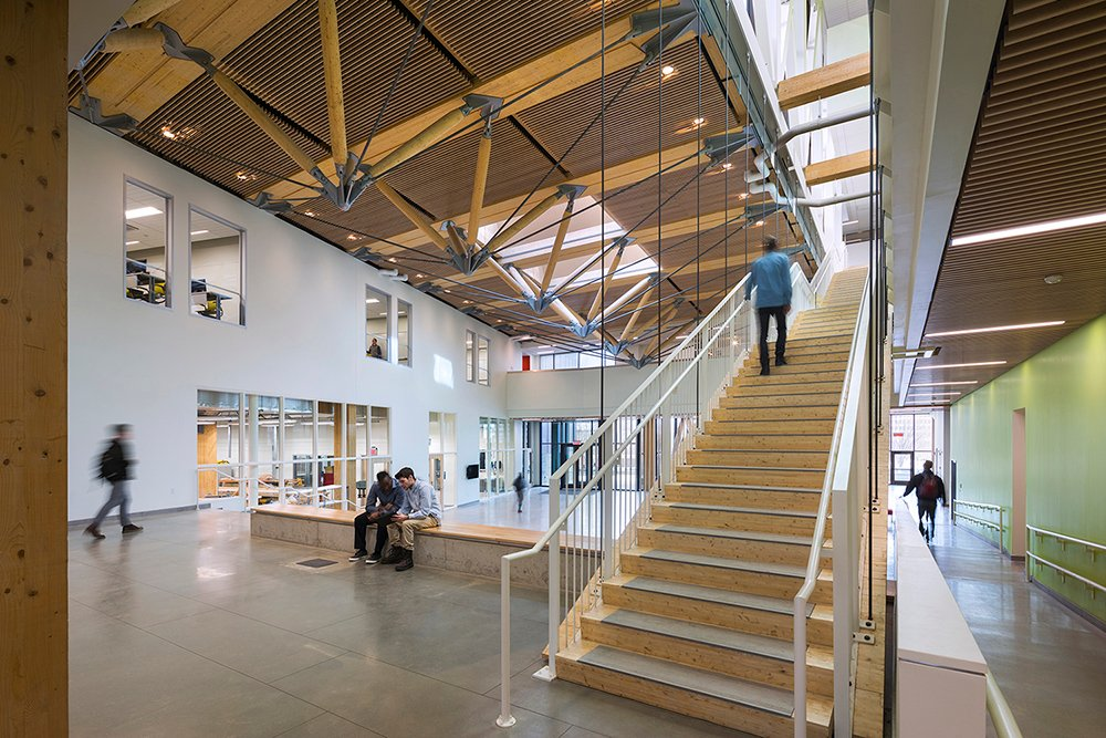 The main stair of CLT panels and glulam tread blocks suspended from the truss above invites visitors through the main Commons and up to the courtyard above Albert Vecerka / Esto