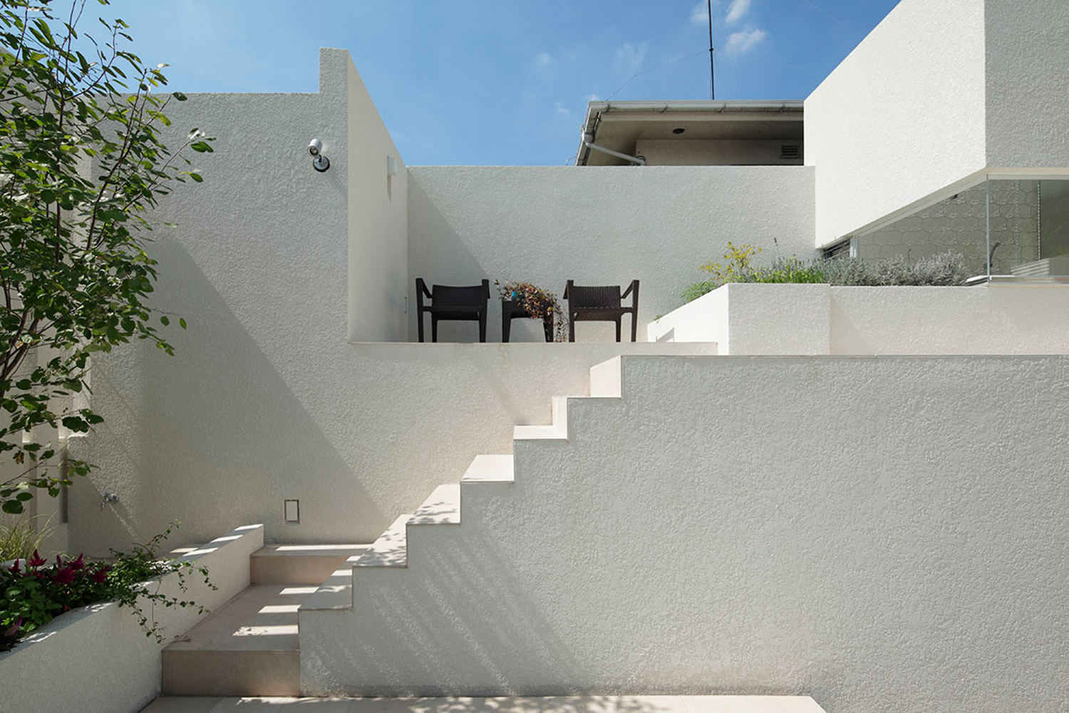 A terrace that is continuous with a white outer wall and a different level. A rich place like a Mediterranean cliff settlement. }