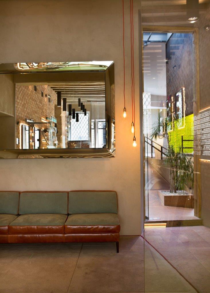 divano Baxter e specchio Caadre per la zona di attesa con lampadine effetto vintage con cavo in seta colorato