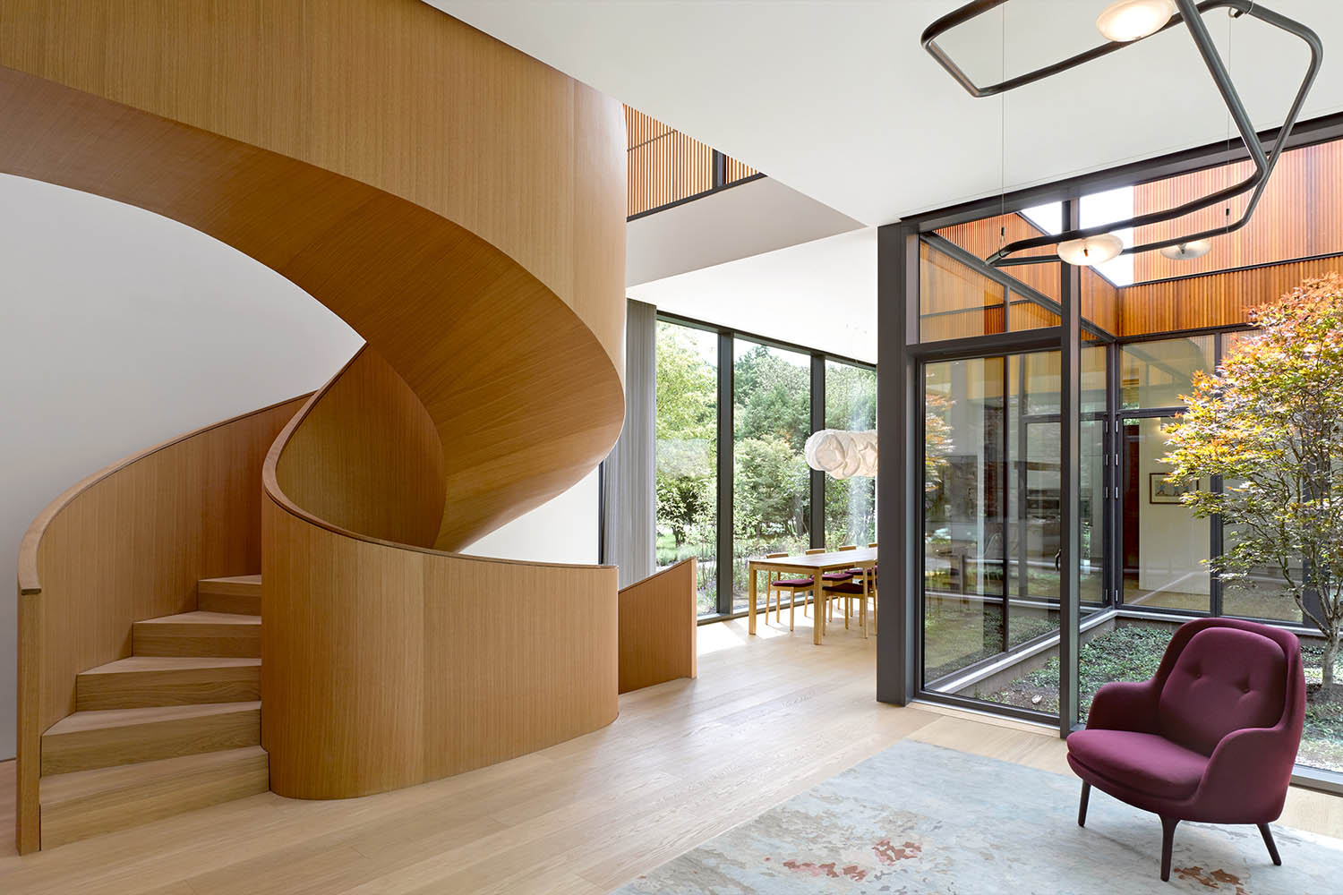 Spaces collapse across the courtyard. View showing the living and dining rooms and spiral stair. Ben Rahn/A-Frame Inc.