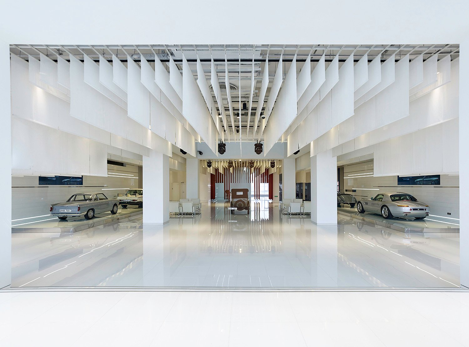 White banners hang from the open ceiling, softening the space and reducing the height to a more intimate scale  YANG Chao Ying