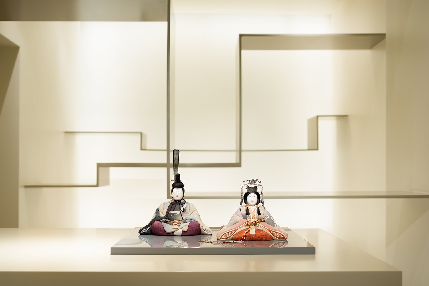 Beishu hina dolls on the center exhibition counter, steel floating shelves in the background. Takumi Ota photography