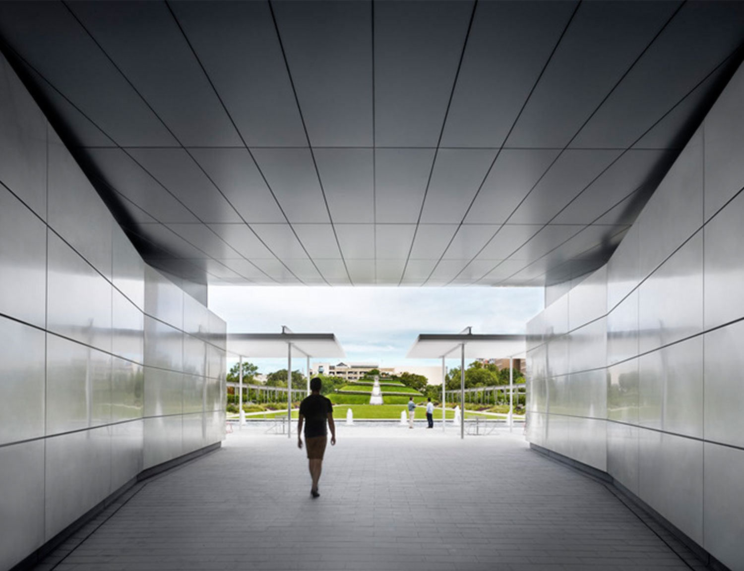The Pavilion makes a threshold to the garden - a magic door you go through to enter another world. The entryway portal's angled stainless steel walls and aluminum ceiling reflect the colors of the sky, ear Casey Dunn