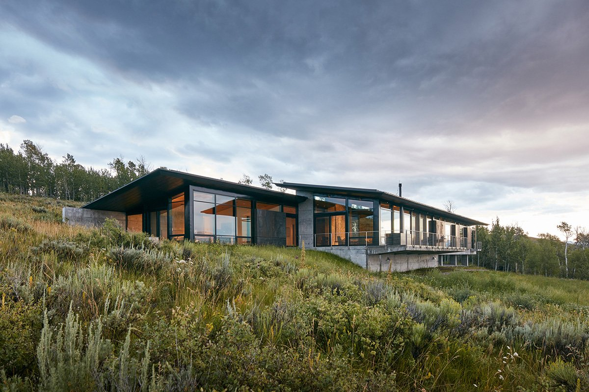 The back of the home is more modest and unobstructive to the beautiful meadow.  Consisting mostly of glass, the views of the adjacent Teton Mountain range are clearly enjoyed from inside.