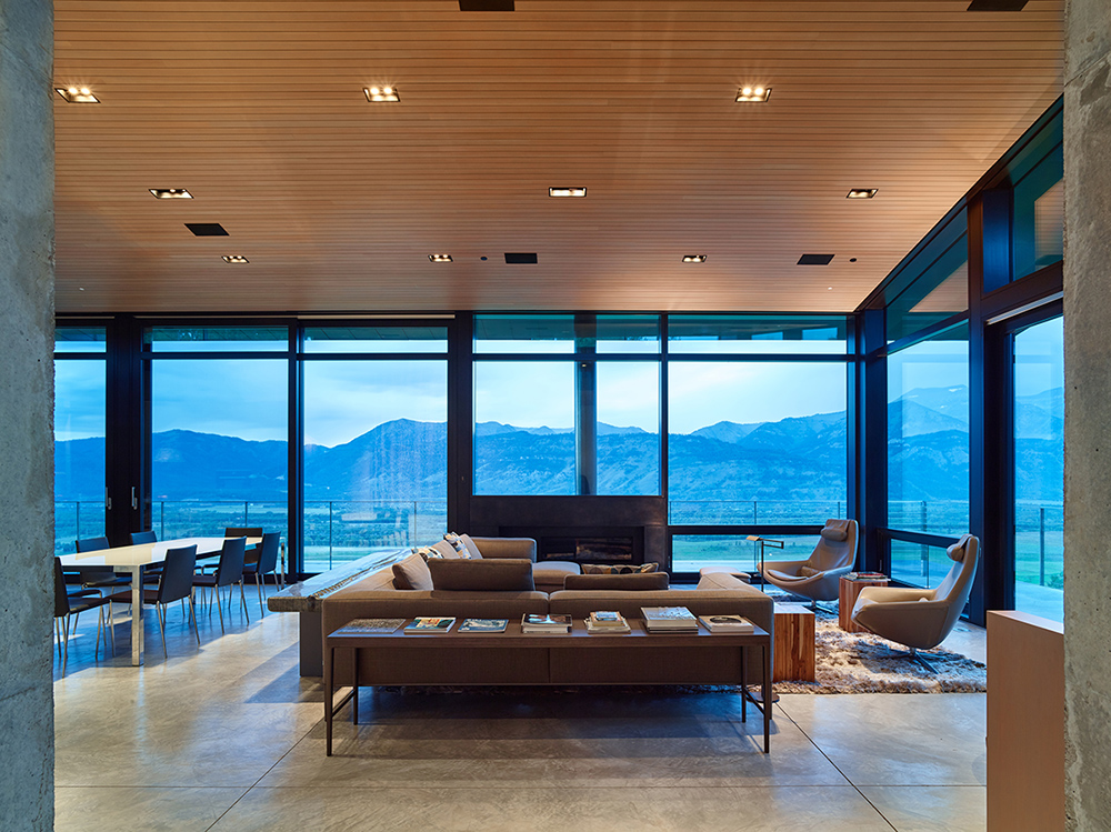 In the living room, the fireplace is maintained low to allow an unobstructed mountain view that reads as a panoramic piece of art.
