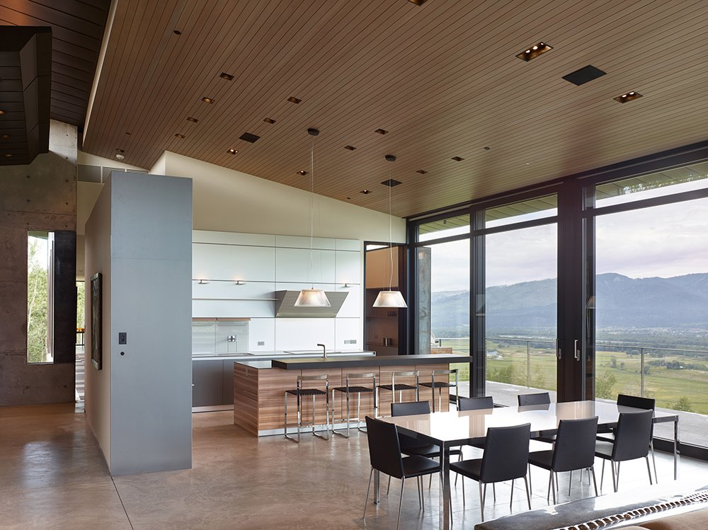 The minimal kitchen design is apportioned with tri-colored cabinets and a clever opening that overlooks the gallery.
