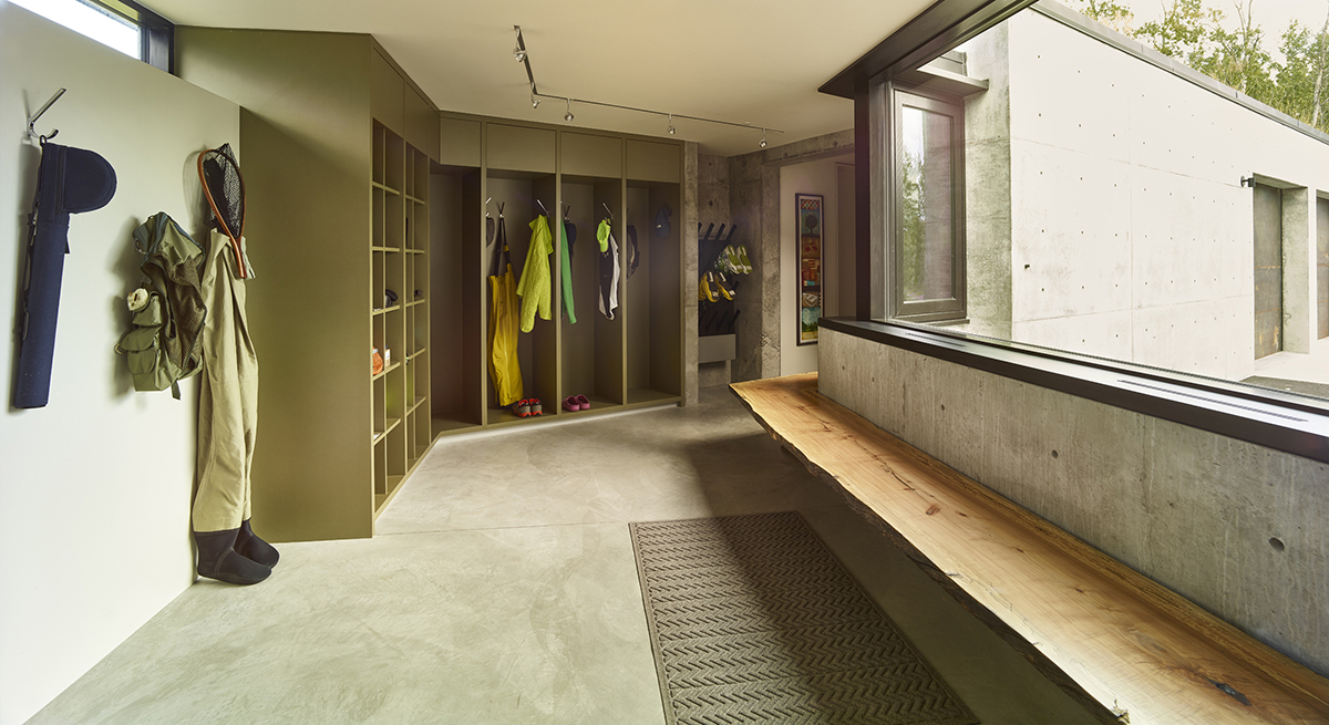 A utilitarian mudroom serves the needs of the family's active lifestyle.  Ski boot warmers hang on the wall and custom storage keeps their gear organized.  A wooden bench inserts charisma, fabricated from