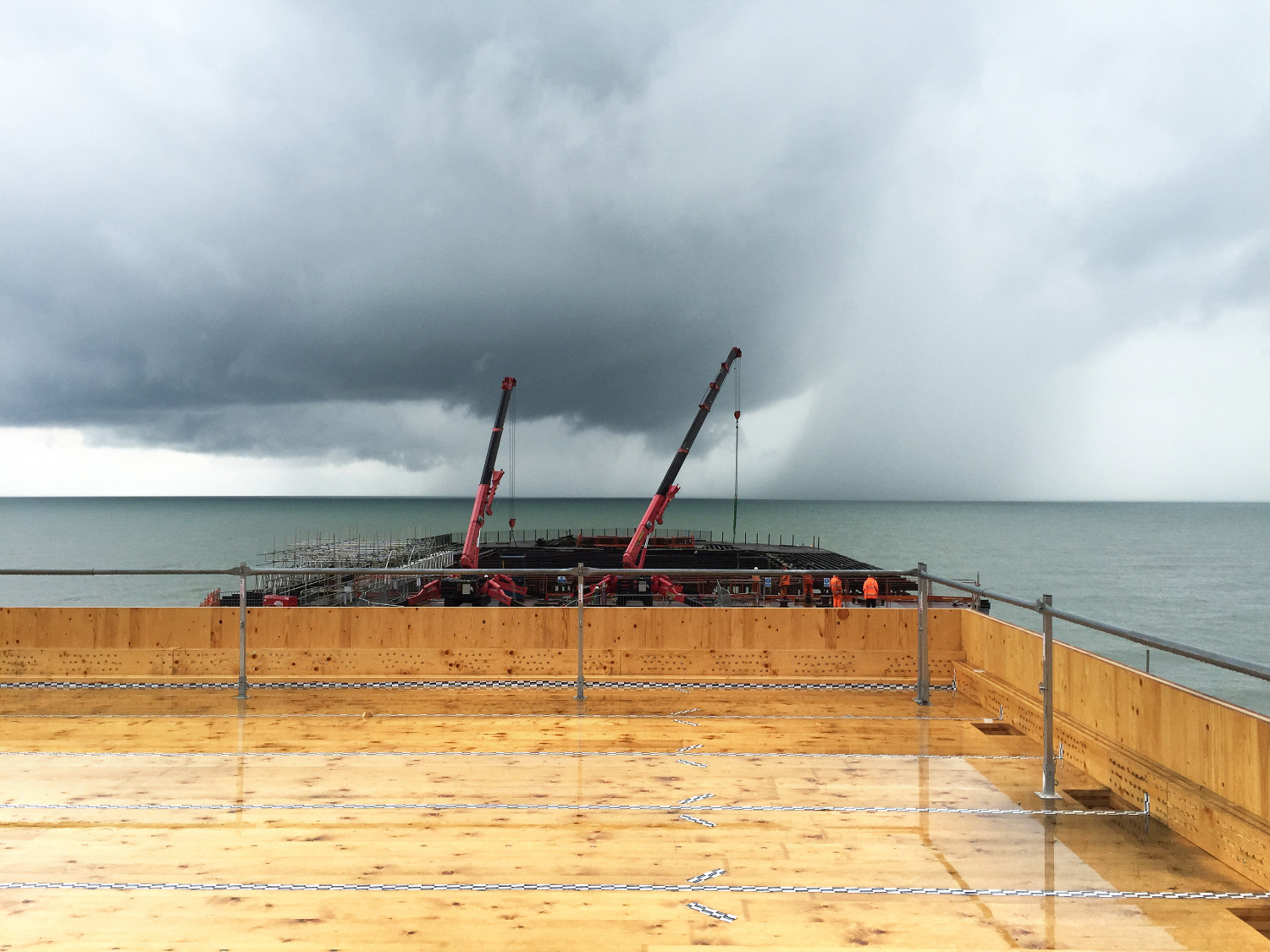 Hastings Pier under construction with barge