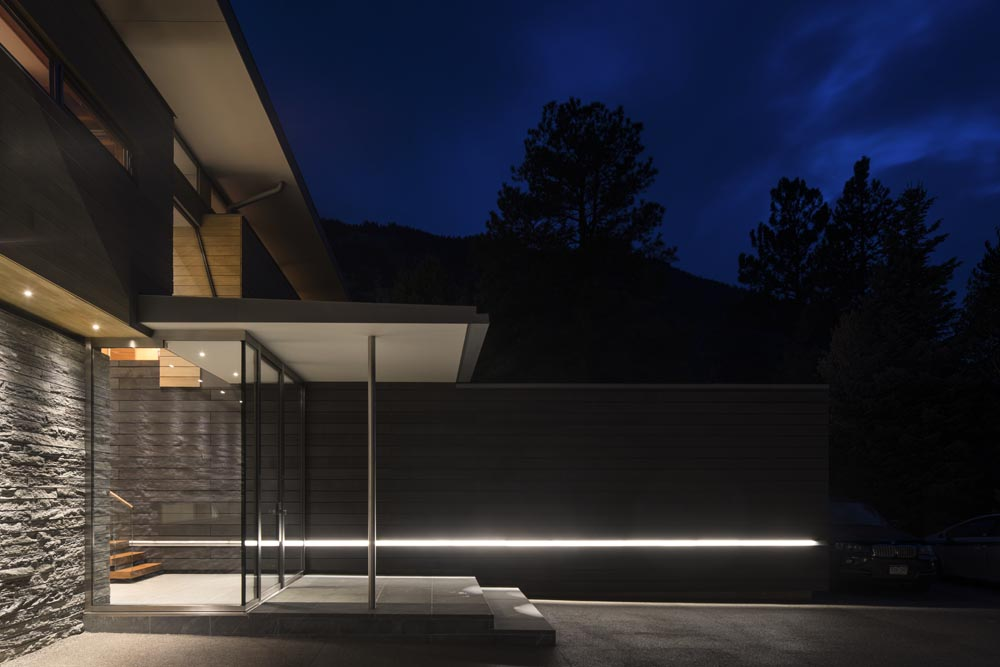 A wall clad in black-stained cedar boards marks the main entry and extends through the house from interior to exterior features a continuous recessed LED light fixture that provides a subtle glow as it gen