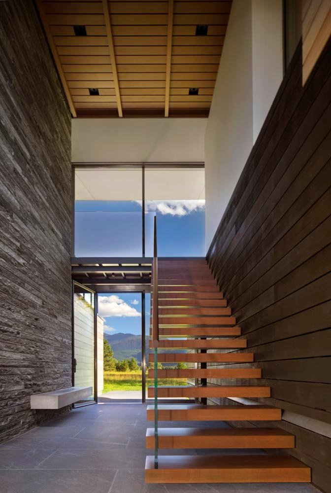 Cantilevered wood stair treads lead to the upper level and main living pavilion where full-height walls of glass reveal panoramic views of the nature preserve and New York Peak.