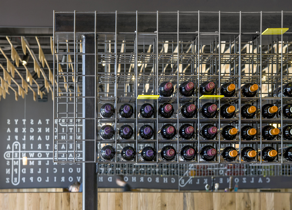 NYPD Tempe Gateway- A custom welded wire mesh wine rack accommodates storage and divides the space.
