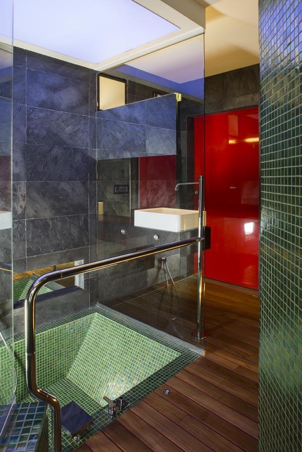 Bagno, pavimento in parquet, vasca realizzata in mosaico verde.