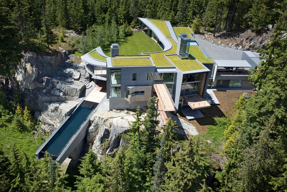 Atop a rocky outcrop high above Alta Lake in Whistler, this private home is nested in the shape and contours of the landscape.   A small spike of the building perched high on a rock ledge overlooks the steeply ascending mountainous drive to the property.