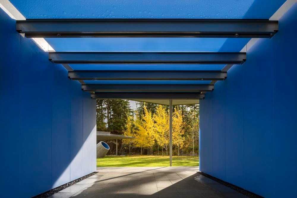 A shimmering blue, glass passageway opens to a verdant courtyard that serves as an oasis for outdoor gatherings and children's play.