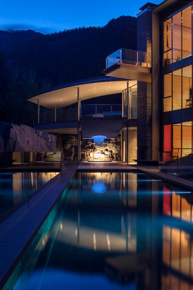 Nestled into a grotto, a spa anchors the 25-meter pool, which slices through and cantilevers over the edge of a rocky precipice intently reaching to the distant horizon.