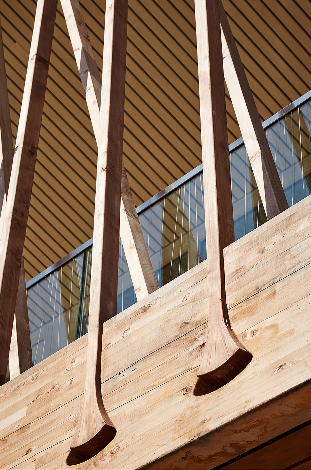 The wood battens are bundled at the glulam beams to minimize the load at mid-span and are offset to distribute the load evenly. The flared detail at the lower cord connects the battens and beams without an
