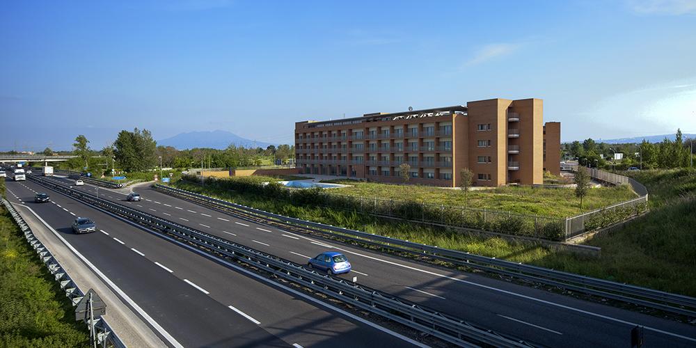 Vista dal cavalcavia autostradale. Il volume si staglia nel paesaggio relazionandosi all'asse autostradale ed all'emergenza paesaggistica del Vesuvio sullo sfondo.