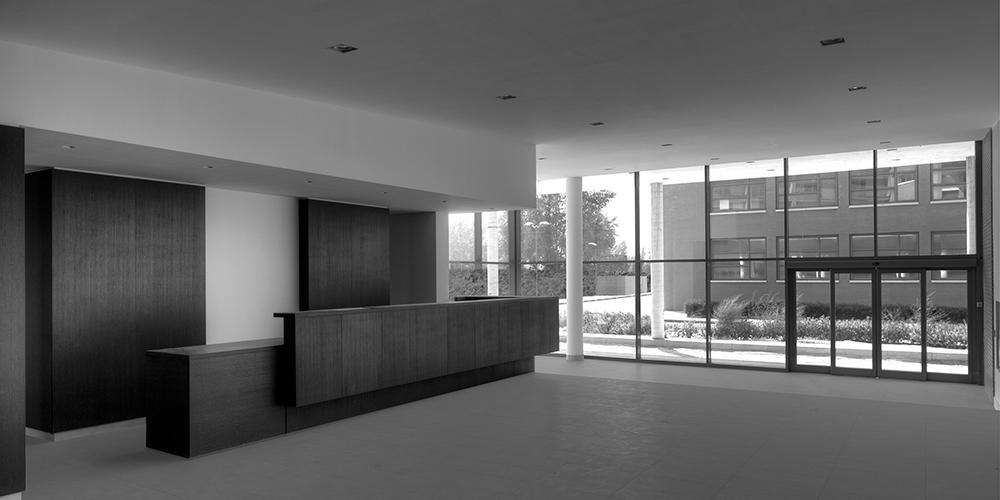 Vista della reception. L' articolazione spaziale sottolinea la sequenza reception/atrio/pensilina d'ingresso, creando una chiara relazione col volume preesistente degli uffici.