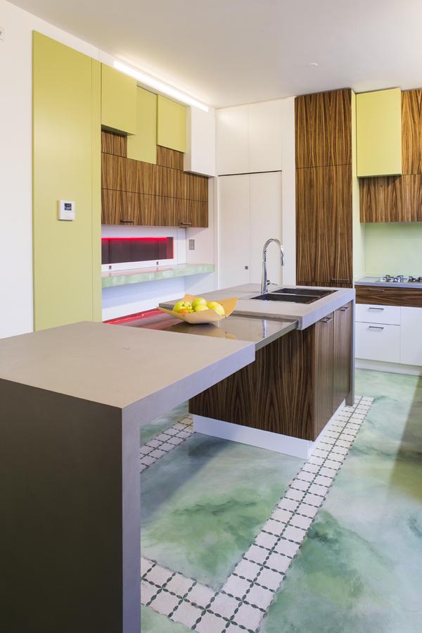 Cucina realizzata artigianalmente con finiture in verde e legno.