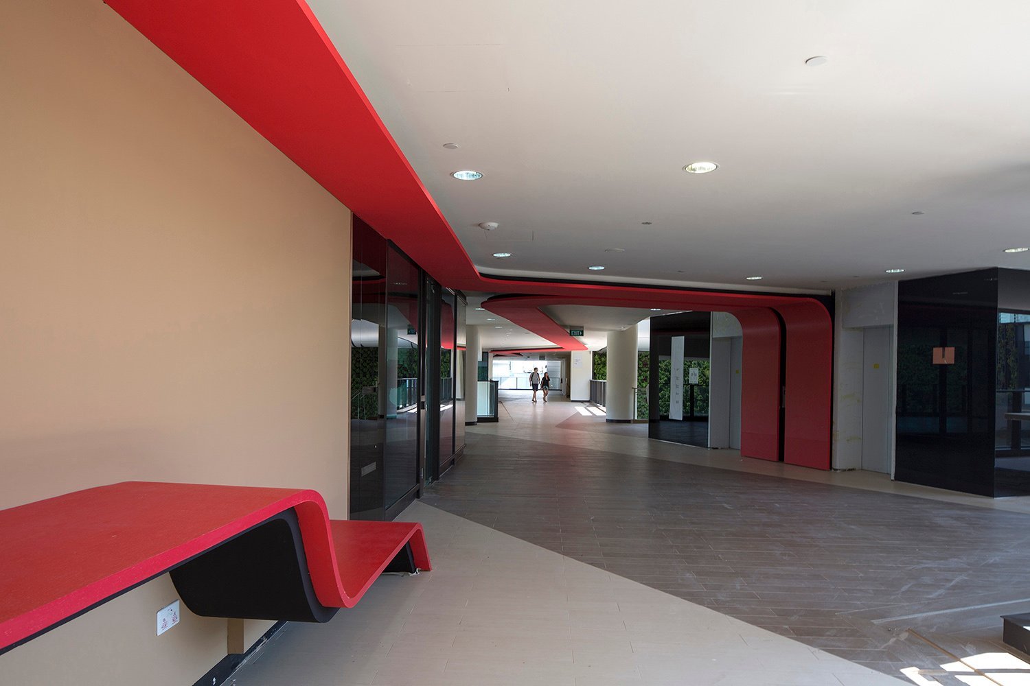 The red ribbon turns down to form feature walls and benches