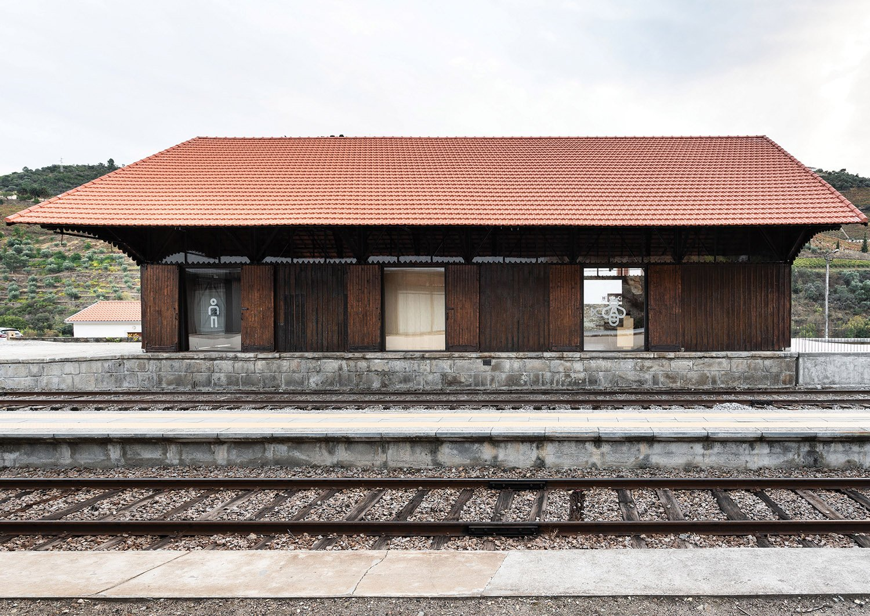 wooden building north facade with vinyl pictograms in the spans Luís Ferreira Alves